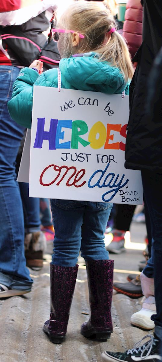 "A little girl in a blue jacket stands amidst adults. She is wearing a poster-sign that says ""'We can be heroes, just for one day.' -David Bowie"""