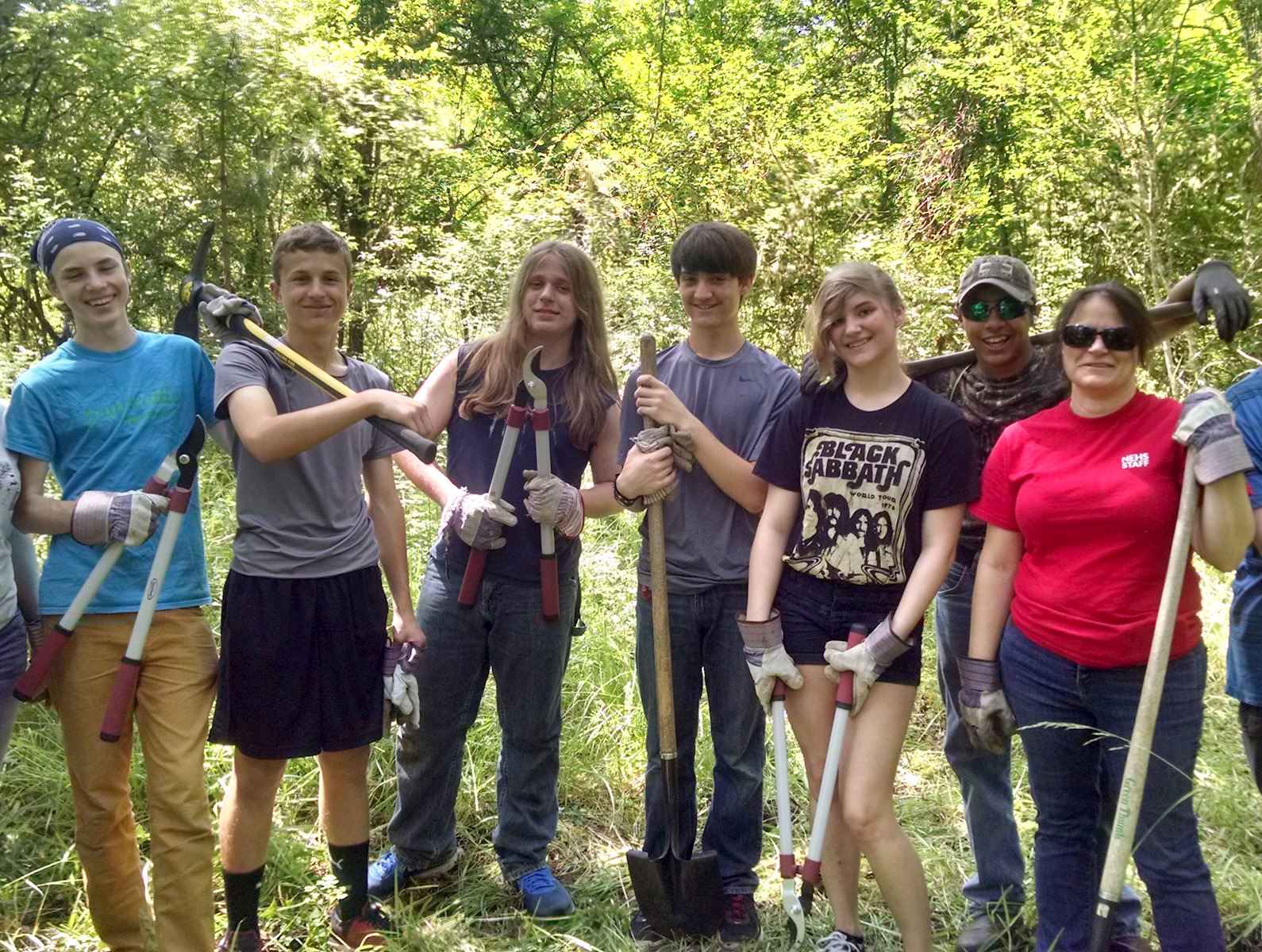A group of high school aged volunteers pose with yardwork tools, smiling at the camera