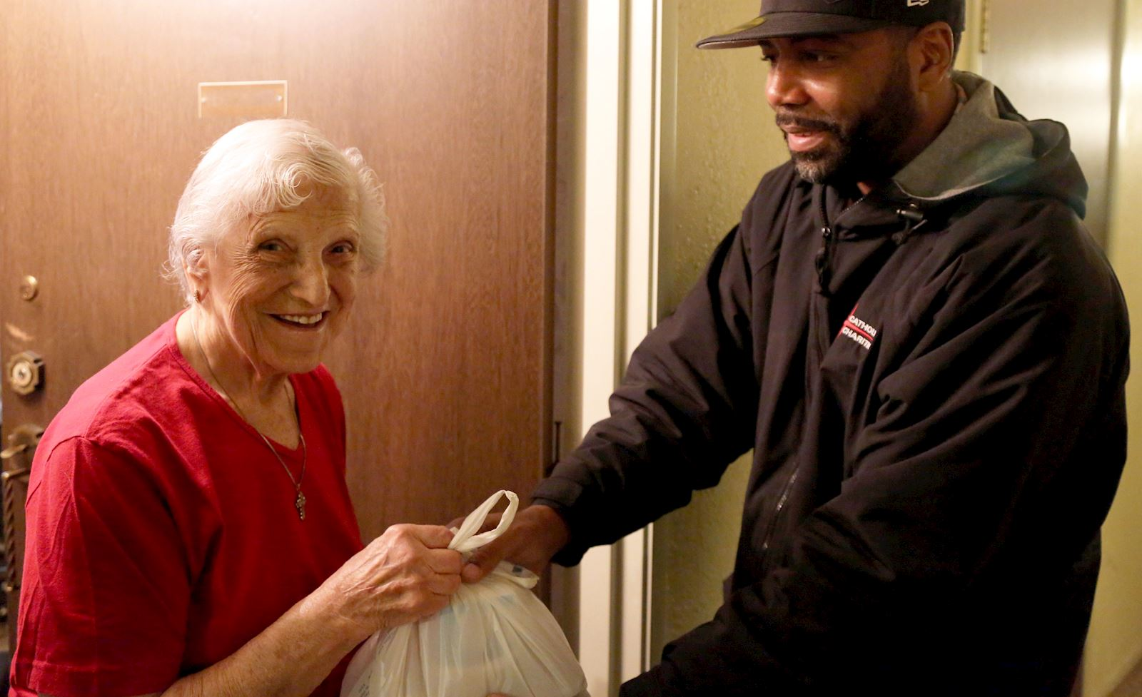 Volunteer delivers a meal to a senior at home