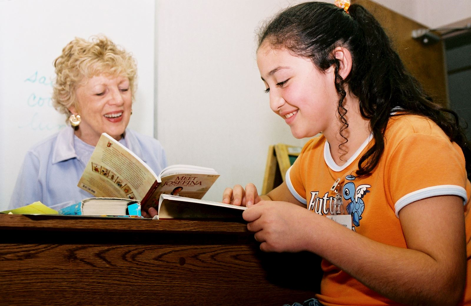 A volunteer reads with a student