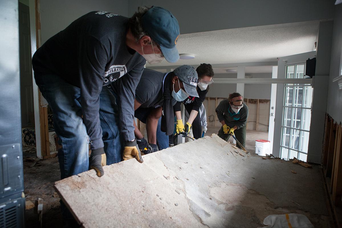 Volunteers help gut a flood-damaged house.