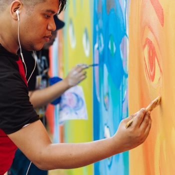 Young man painting a colorful mural