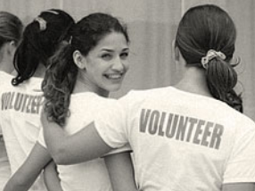 Woman volunteers in white shirts embracing