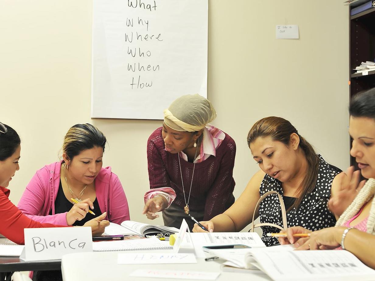 A volunteer helps teach English