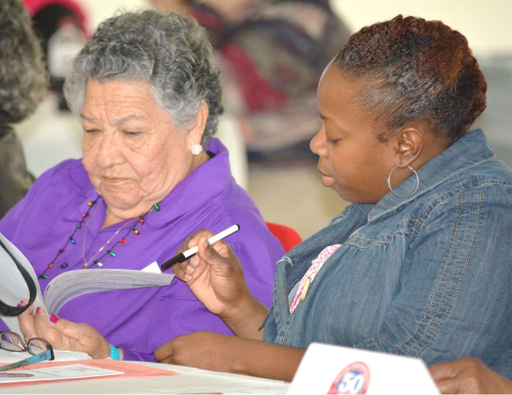 An African American woman points out text on a document. An gray-haired elderly woman looks on.