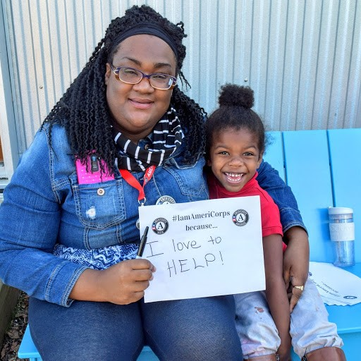 "A young adult woman sits on a bench with a preschool girl. The woman holds a sign that says ""I am AmeriCorps because I love to help!"""