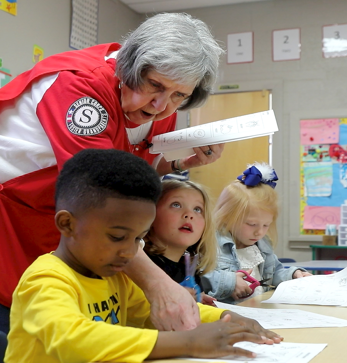 An ederly woman with grey hair leans over a group of preschool students as they sit at a table. The woman has papers in her hand and is pointing to a paper on the table.